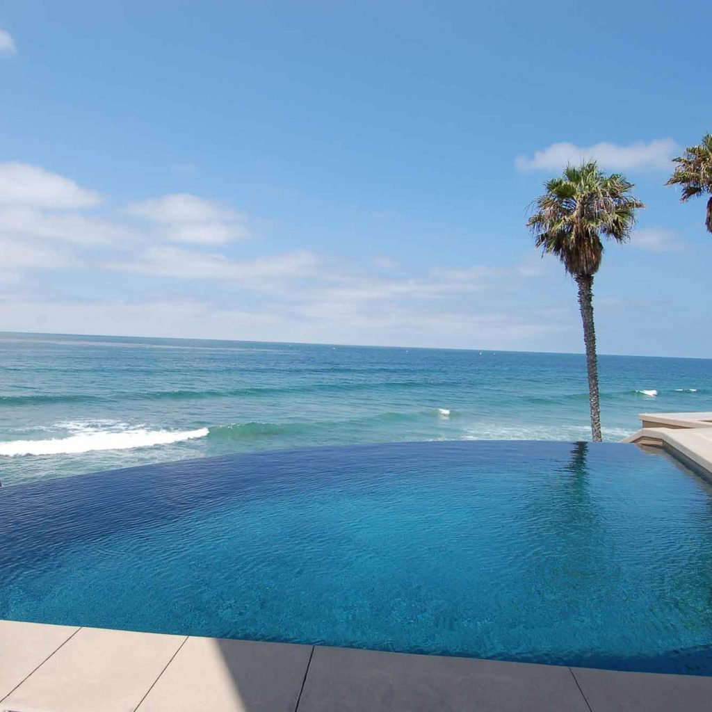 Amazing infinity edge pool over looking the ocean with palm trees in foreground.