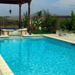 A geometric pool with spa underneath a gazebo.