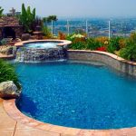 A freeform pool with a raised rock spa overlooking the San Diego landscape.