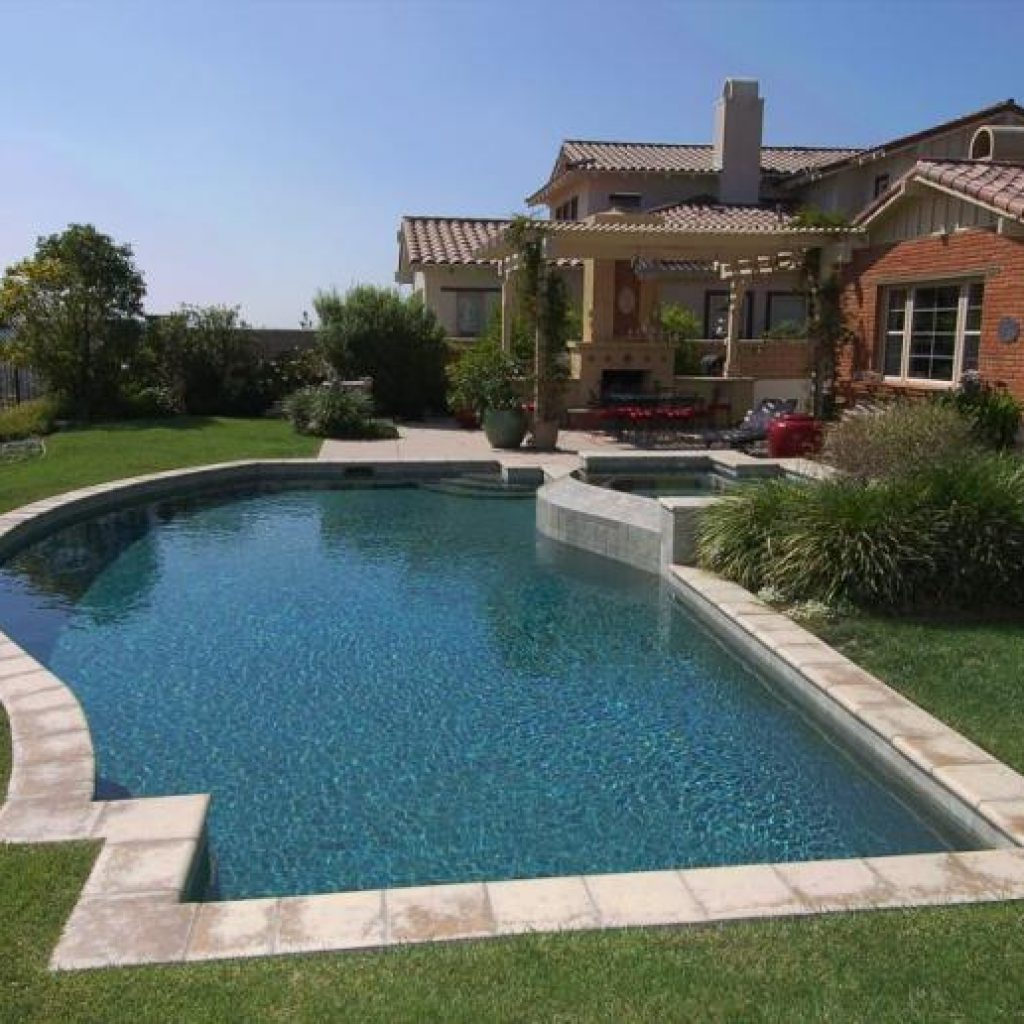 Freeform pool and spa with green lawn.