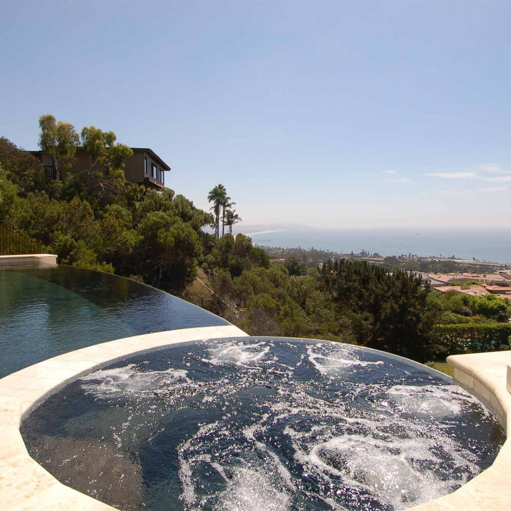 Close up of bubbling custom spas with an infinity edge pool.