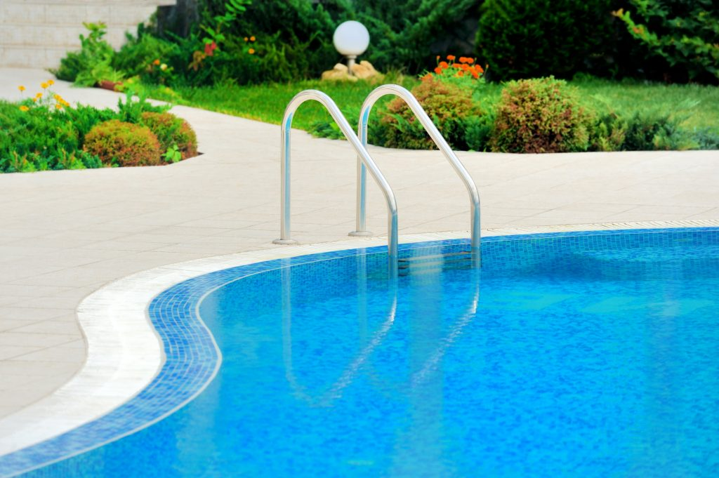 A closeup of a freeform swimming pool with a pool ladder.