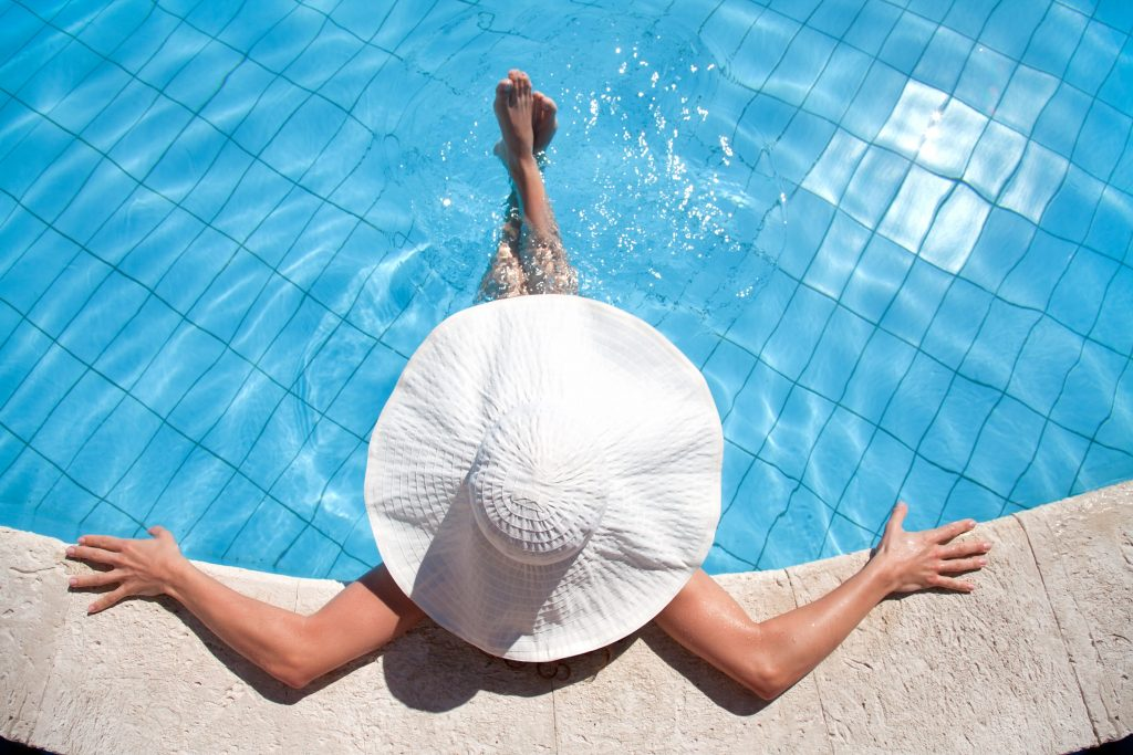 A photo that is looking down ontop of a woman lounging in a pool with a large white sun hate on.