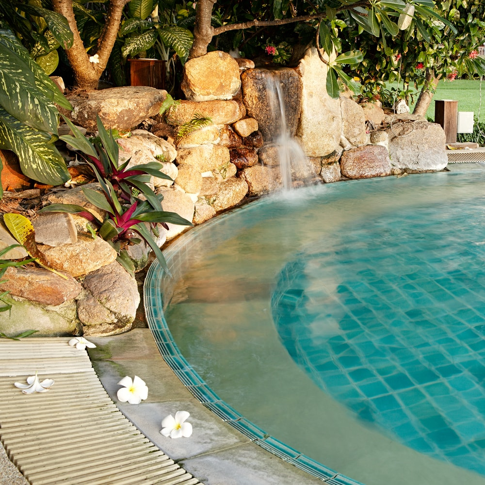 Natural rock pool designs can set your home aside from for Natural rock swimming pools