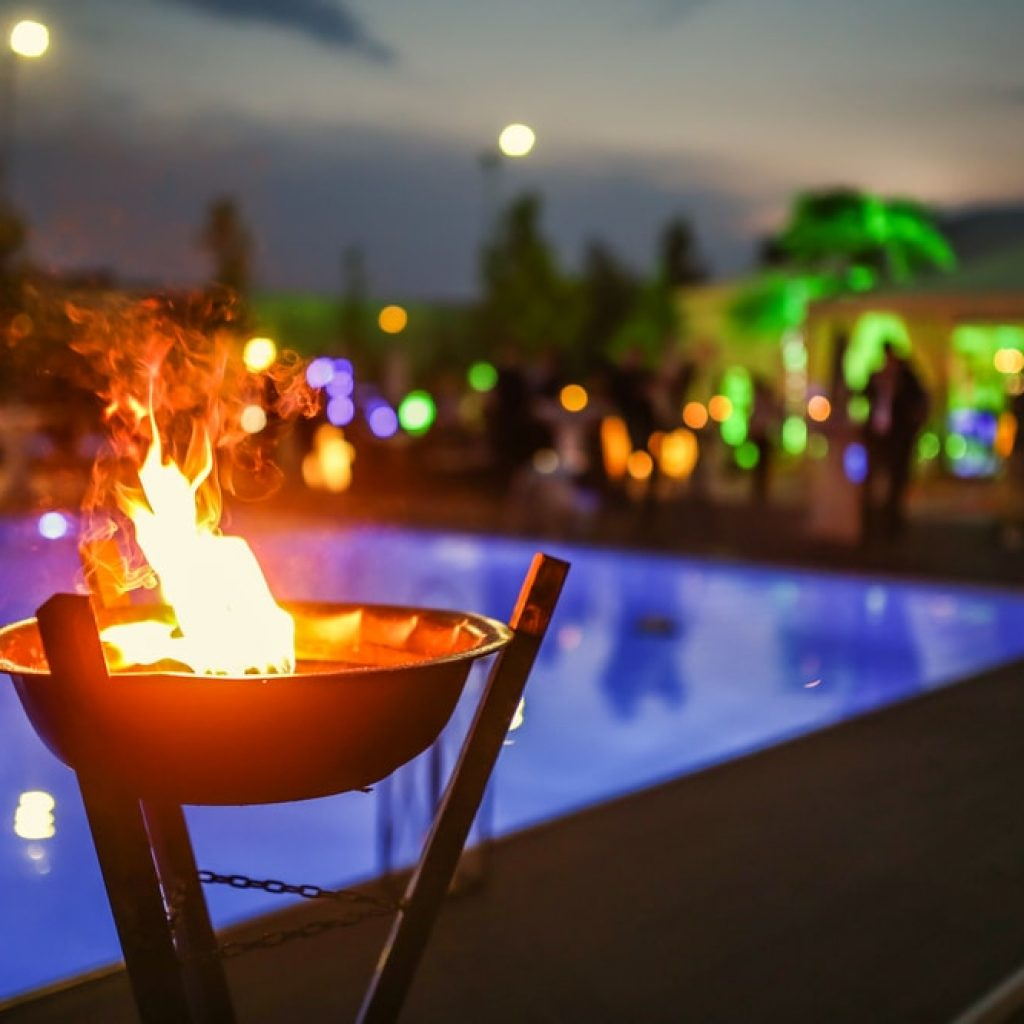 A close up of a fire feature with a pool and party goers in the background at night.