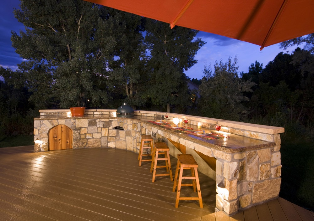 A backyard kitchen is integrated into the landscaping design.